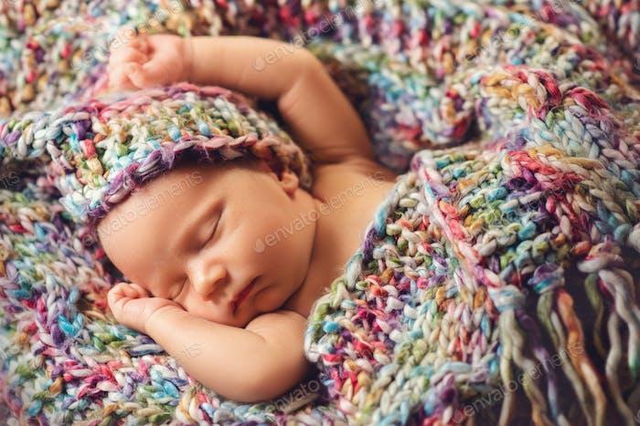 Newborn baby sleeps in a knitted scarf