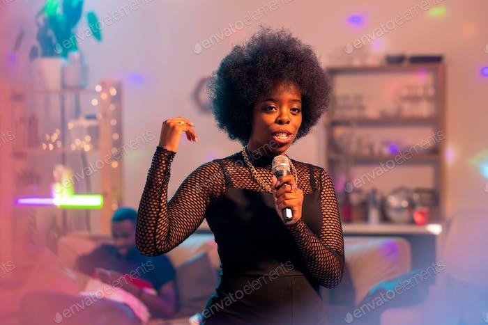 Young elegant woman in elegant black dress singing karaoke in microphone