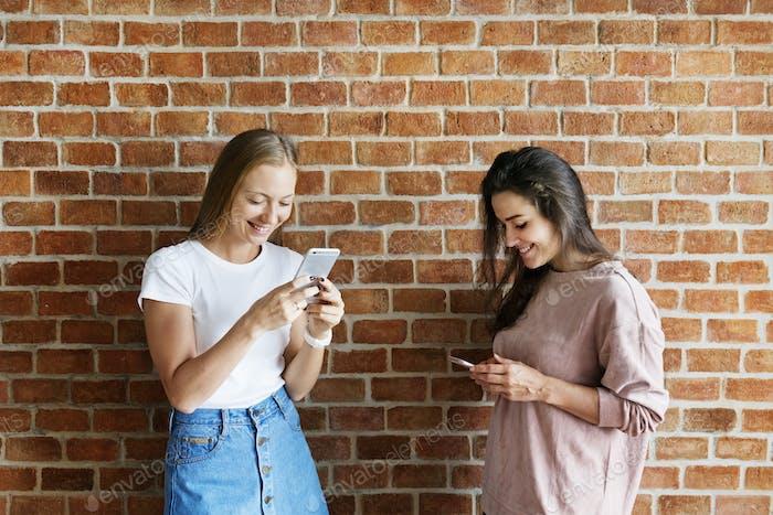 Happy female friends using smartphones