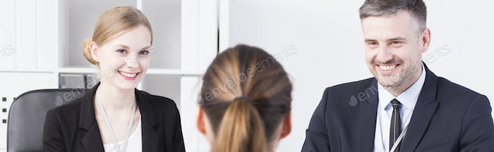 Smiling recruiters talking to applicant
