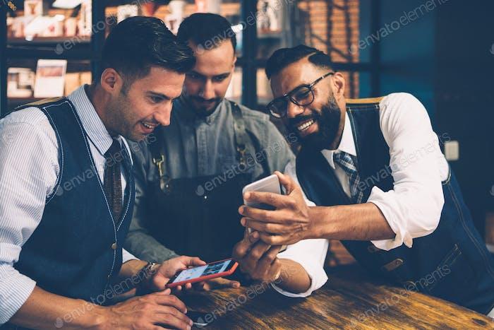 Smiling men looking at smartphone