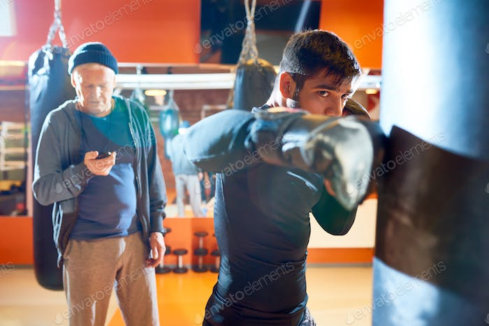 Man boxing bag with trainer on workout