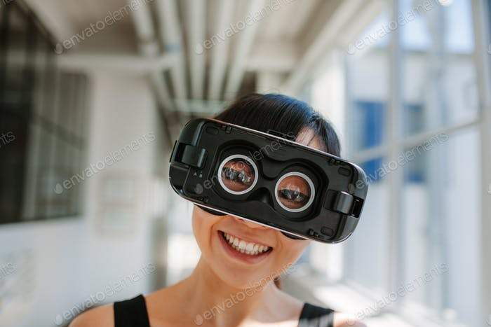 Cheerful young woman wearing virtual reality goggle