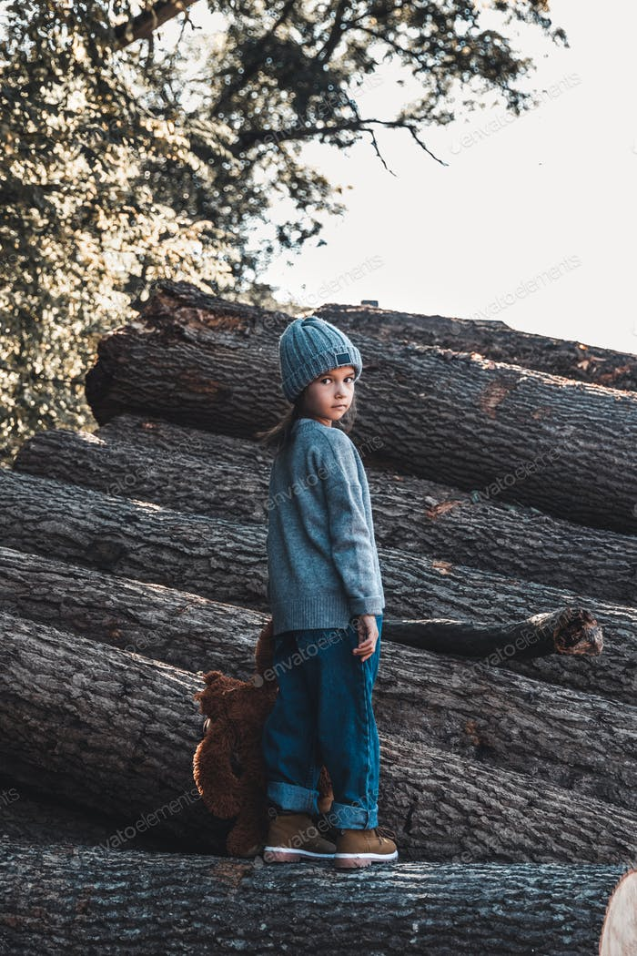 Little girl with a teddy bear standing on the logs