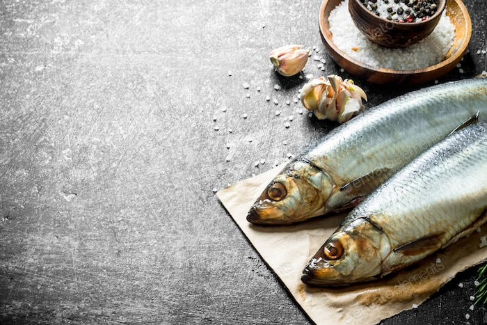 Salted herring on paper with garlic and spices.