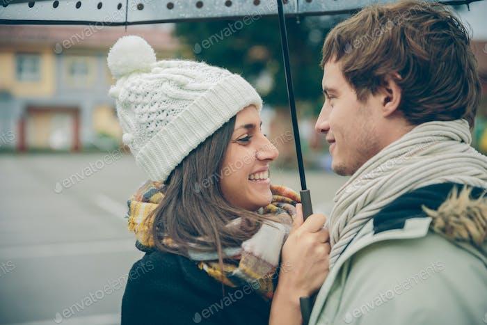 Pareja joven abrazando y riendo al aire libre bajo el paraguas