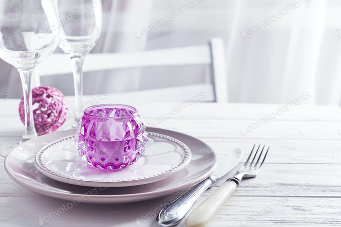 Purple Christmas table setting with candlestick and glasses of wine above light window