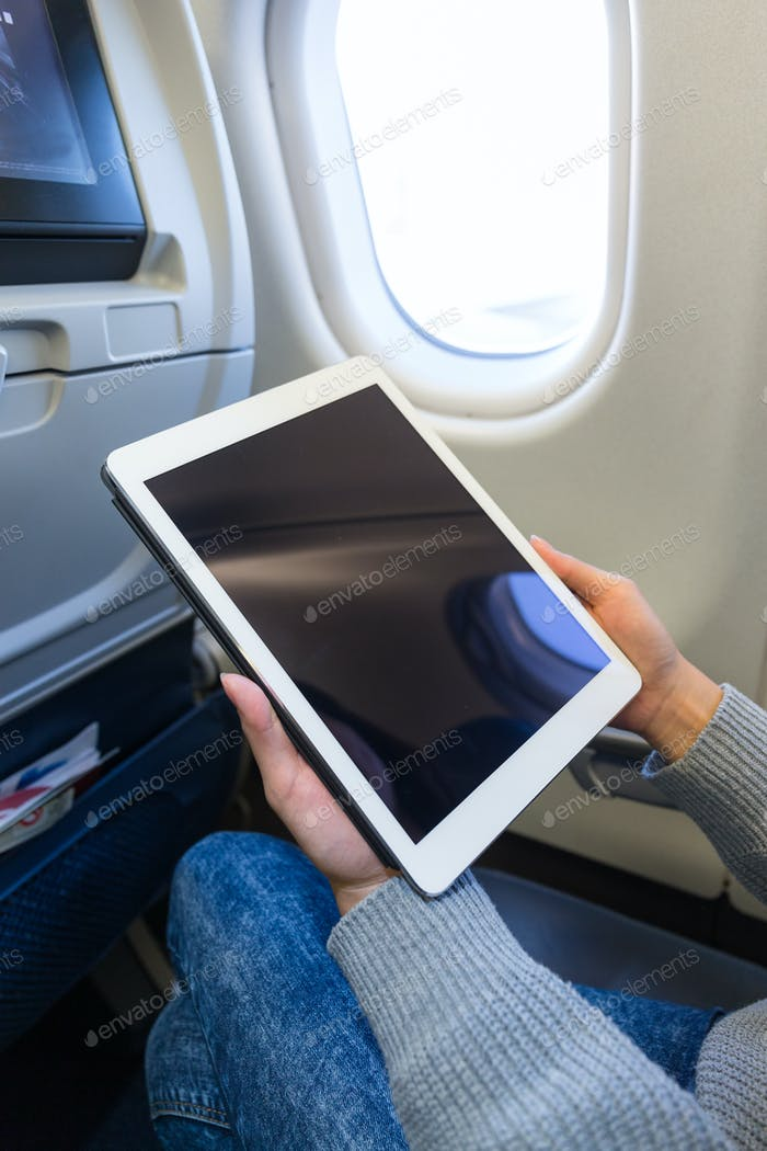 Woman use of tablet pc inside aircraft