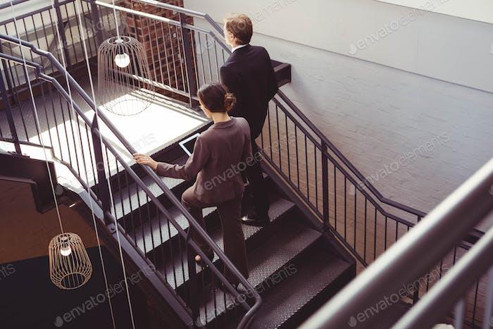 Два хорошо одетых бизнесменов поднимаются по лестнице офиса