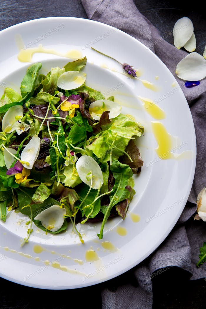 Healthy lettuce arugula salad with edible flowers and microgreens on white plate