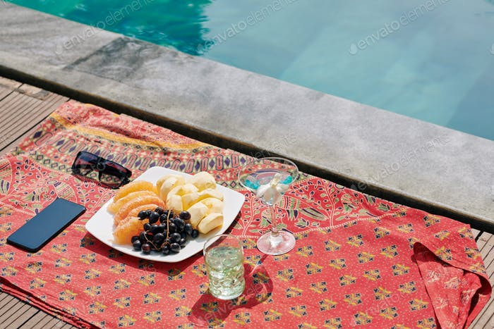 Fruits and cocktails by swimming pool