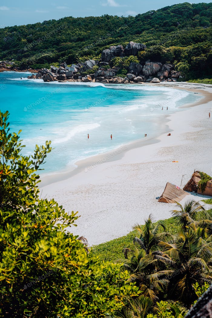 Beautiful Grand Anse beach with unrecognizable tourist people on La Digue island in Seychelles