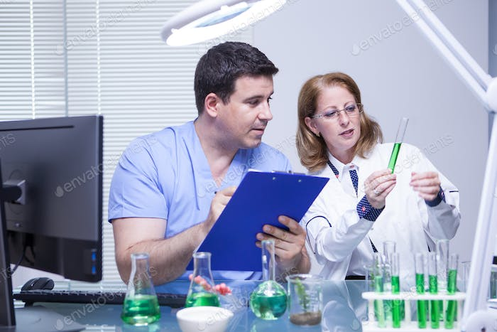 Scientists in biotechnology checking the solution from a test tube