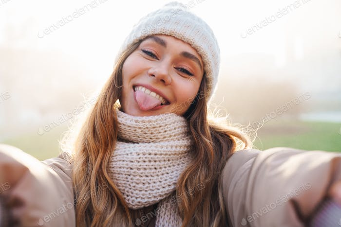 Close up of a cheerful pretty young girl wearing winter jacket