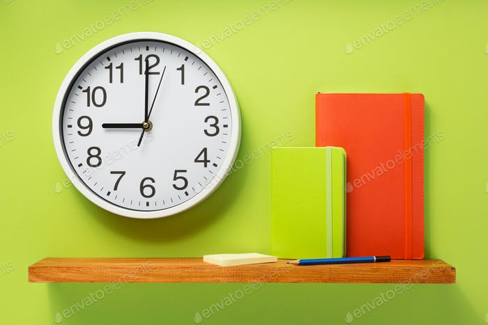 notebook and wall clock on shelf at wall background
