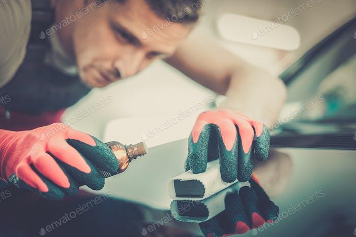 Arbeiter auf einer Autowaschanlage Anwendung Nano-Beschichtung auf einer Motorhaube