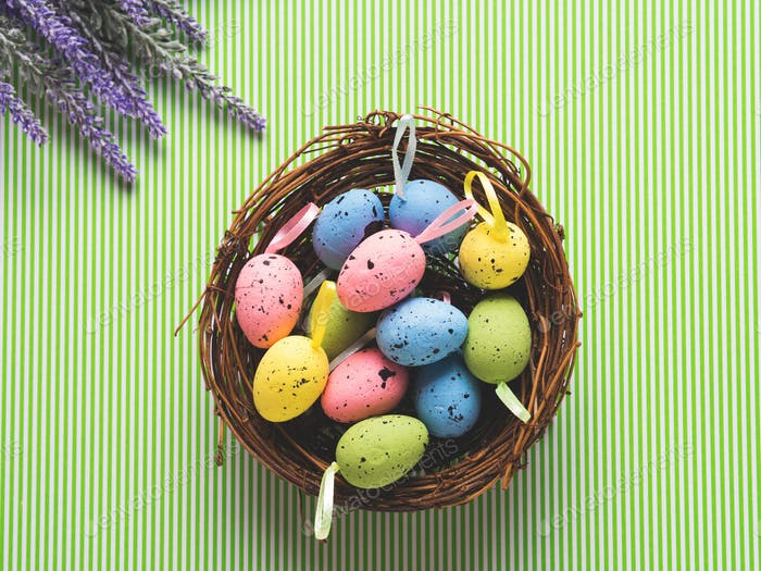 Basket of decorative Easter eggs on green
