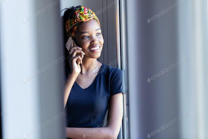 Hübsche junge Frau, die auf dem Handy spricht, während sie zu Hause durch das Fenster schauen.
