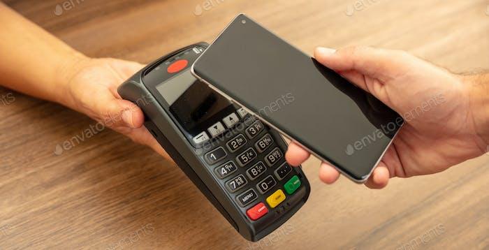 POS-терминал для оплаты со смартфоном, технология nfc. Кассир и руки клиента