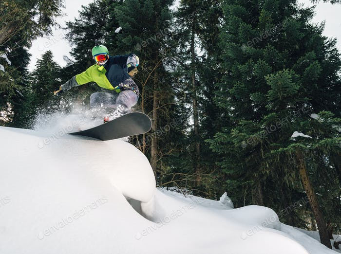 snowboarder with special equipment is riding and jumping very fast in the mountain forest