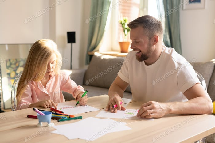 Cute little pre-elementary schoolgirl and her father drawing together at home