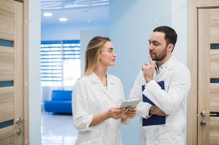Two doctors discussing diagnosis while walking