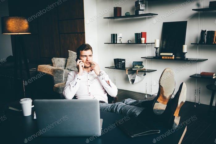 Nachdenklicher Mann sitzt mit Füßen auf dem Tisch und telefonieren im modernen Büro.