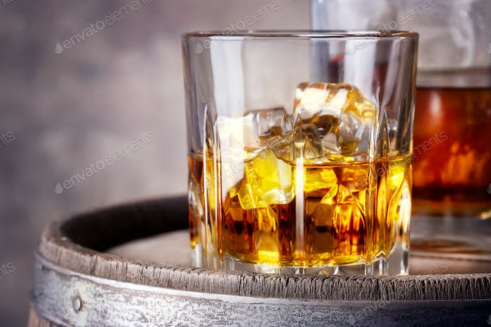 Faceted glass of whiskey with ice
