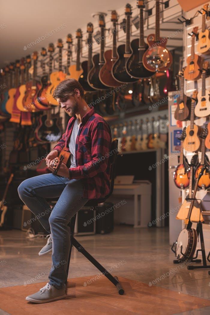 Young man playing on a ukulele
