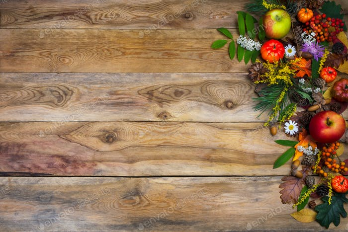 Fall background with pumpkin and green leaves on wooden table