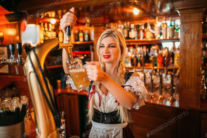 Sexy waitress pours beer into a mug at the counte