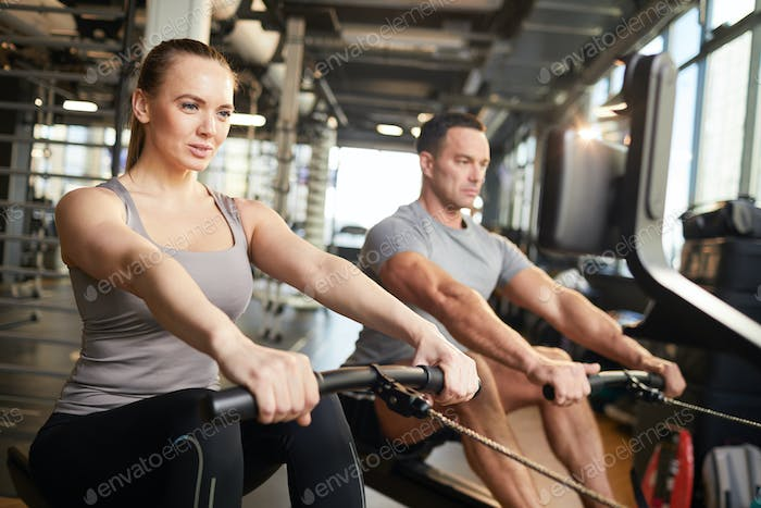 Couple Using Exercise Machine in Gym