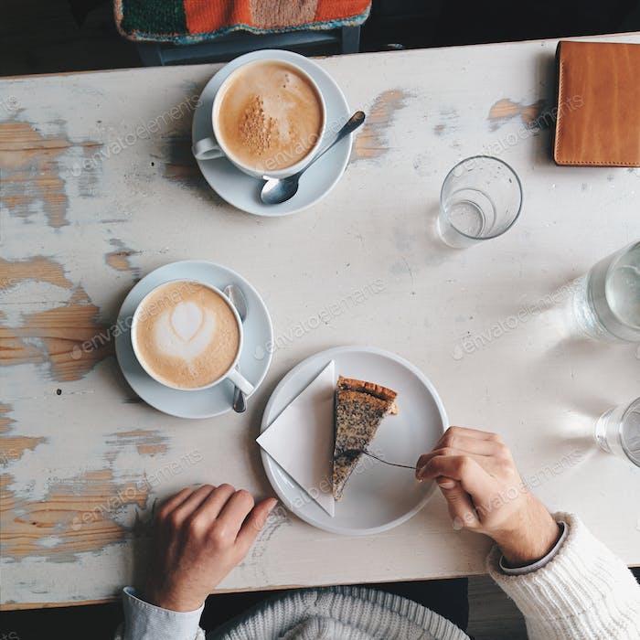 Weißer und brauner Kaffee mit Kuchen-Szene