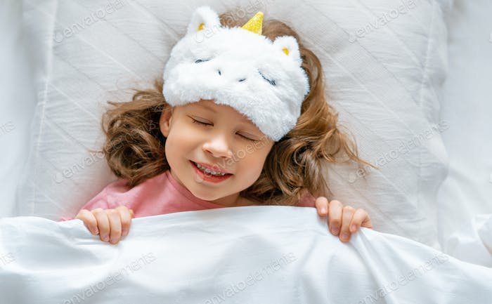 child is sleeping in the bed