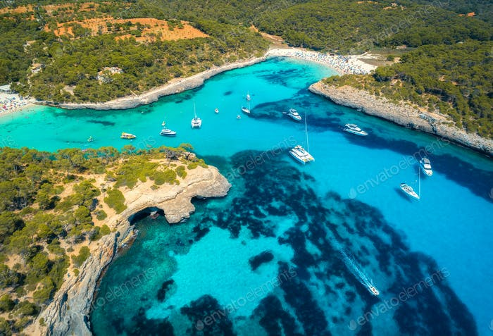 Boats and luxury yachts in transparent sea at sunny day. Aerial