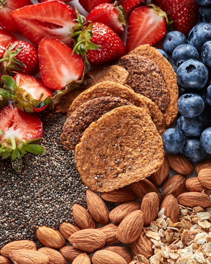 Fresh organic ingredients for dietary homemade natural breakfast - berries, granola, nuts, chia