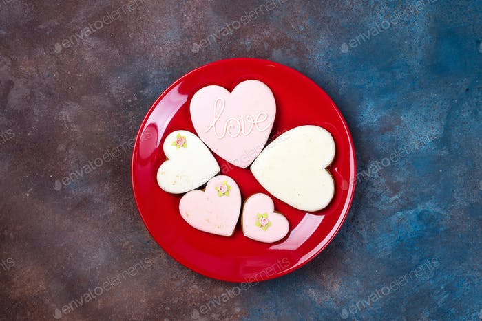 top view of glazed heart shaped cookies on red plate isolated on stone, flat lay. Happy Valentines