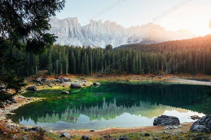 Grüne Tanne auf der linken Seite. Herbstlandschaft mit klarem See, Tannenwald und majestätischen Bergen