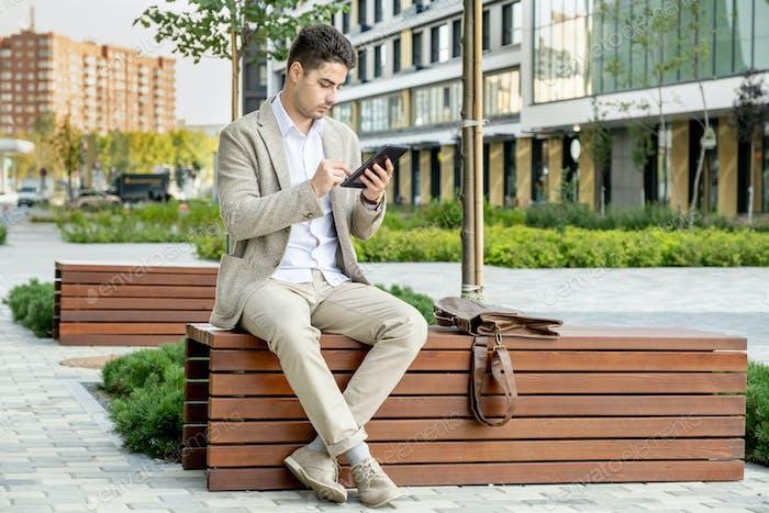 Young elegant restful businessman in formalwear sitting on wooden bench in park