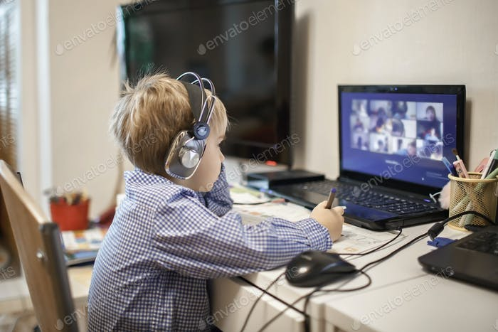 Distant education, online class meeting. Preschool boy studying during online lesson at home