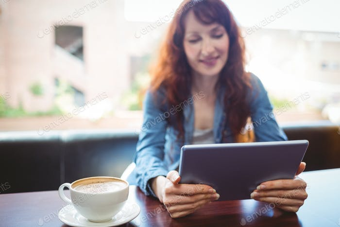 Mature student using tablet in cafe at the university