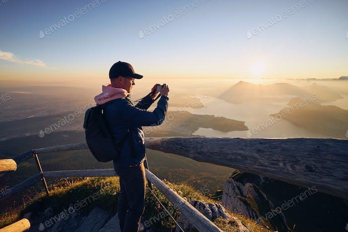 Man photographing landscape at beautiful sunrise
