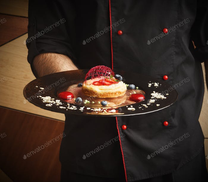 Lemon cheesecake with berry spheres served at modern restaurant