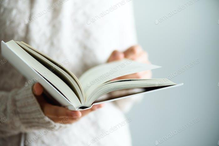 Junges Mädchen in weißem T-Shirt Lesen geöffnet Buch. Kopierraum. Lifestyle und Schulkonzept