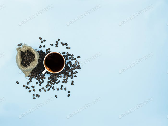 top view black coffee and coffee beans bag on blue background