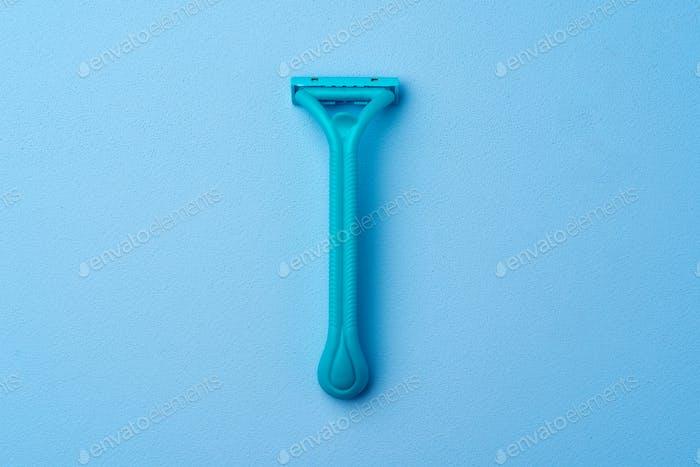Single disposable razor for women on blue background
