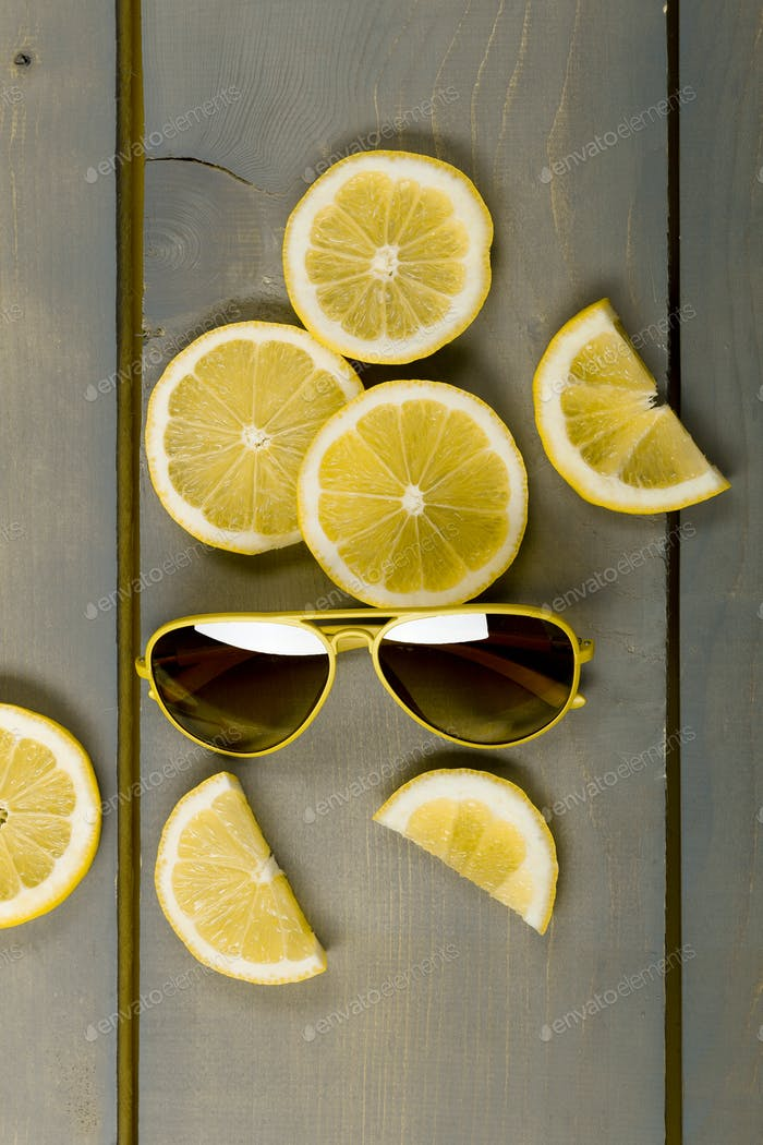 sunglasses on wooden background, top view. Yellow aviator sunglasses near lemon on grey wooden