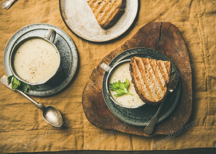 Flat-lay of warming celery cream soup and grilled bread