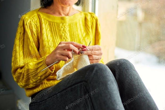 Mature female sitting on the windowsill and knitting