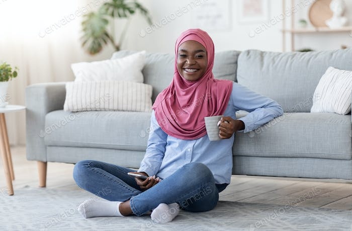 Smiling Black Islamic Woman Relaxing On Floor With Smartphone And Coffee